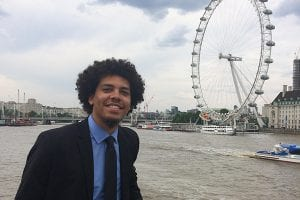 An Honors College student, wearing a suit, stands in front of the River Thames and the London Eye ferris wheel in London, England.