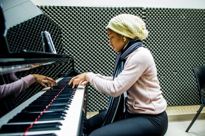 A student plays piano in a soundproof studio